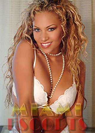 Curly haired escort poses in white for escort service Miami Beach.